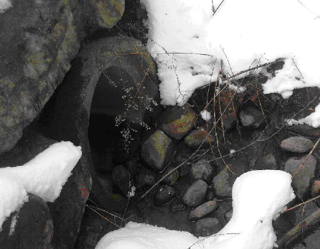 Stones and snow at mouth of a runoff drain